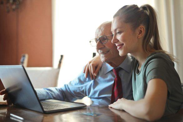 Image of women helping older man with laptop