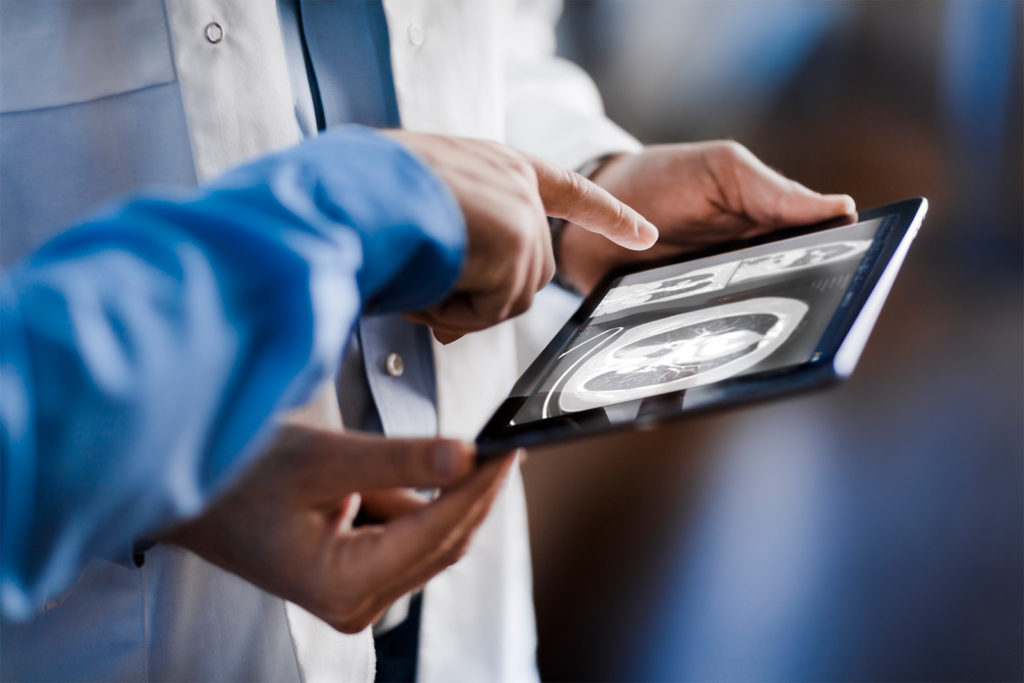 Close-up of a doctor showing a colleague or patient medical images on a tablet using Sectra UniView.